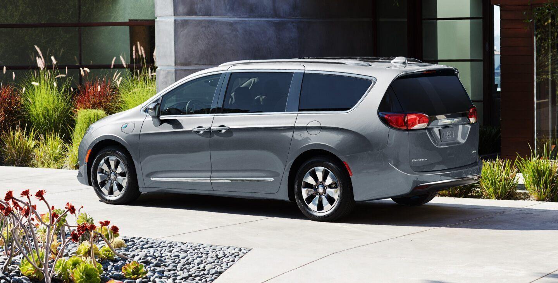Se muestra una Chrysler Pacifica Hybrid 2020 estacionada en la entrada frente a una casa.