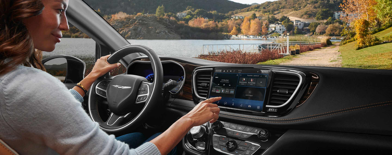 El conductor en unaChrysler Pacifica Limited2021 con una mano en el volante y con la otra realiza una selección en la pantalla táctil Uconnect.